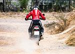 Man riding his scrambler type enduro motorbike on dirt track, rear view, Bangkok, Thailand