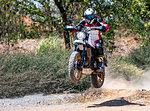 Man jumping with his scrambler type enduro motorbike on dirt track, rear view, Bangkok, Thailand