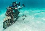 Diver posing with submerged motorbike, Ko Racha Yai, Rawai, Phuket, Thailand