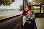Mother and baby looking out window of motorhome, Wanaka, Taranaki, New Zealand
