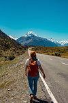 Hiker walking towards mountains, Wanaka, Taranaki, New Zealand