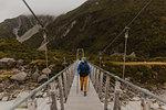 Hiker crossing suspension bridge, Wanaka, Taranaki, New Zealand