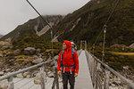 Hiker with baby crossing suspension bridge, Wanaka, Taranaki, New Zealand