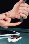Using blood sugar testing lancet on finger.