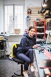 Portrait of mature female technician sitting in electronics store