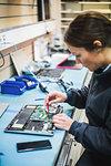Mature female engineer repairing equipment in computer store