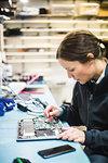 Female engineer repairing computer equipment in workshop