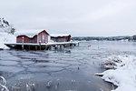Houses above frozen lake in Alback, Sweden