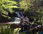 Men sitting on rocks by waterfall