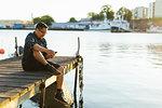 Man sitting on jetty using smart phone