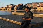 Man sitting on boardwalk using smart phone