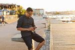 Man using smart phone by boardwalk