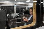 Woman using smart phone on train