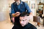 Hairdresser styling customer's hair in barber shop