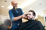 Hairdresser shaving customer's hair in barber shop