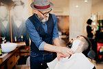 Hairdresser shaving customer's beard in barber shop