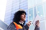 Female surveyor using digital tablet outside office building