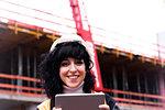 Female surveyor using digital tablet on construction site, portrait