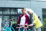 Mature woman and daughter looking at city bicycles at bike park