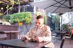 Young man reading book at cafe, Milano, Lombardia, Italy