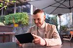 Young man using digital tablet at cafe, Milano, Lombardia, Italy