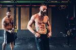 Young tattooed men training in gym, taking a break