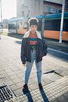 Cool young woman on sunlit urban sidewalk, portrait