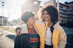 Two cool young female friends on sunlit urban sidewalk, portrait