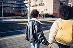 Two young female friends strolling on urban sidewalk, rear view