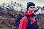 Male hiker in knit hat by snow capped mountains, portrait, Llanberis, Gwynedd, Wales