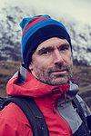 Male hiker in knit hat by snow capped mountains, close up portrait, Llanberis, Gwynedd, Wales