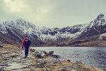 Male hiker hiking alongside lake landscape with snow capped mountains, Llanberis, Gwynedd, Wales