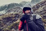 Male hiker with hood up in sleeting snow capped mountain landscape, portrait, Llanberis, Gwynedd, Wales
