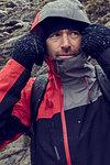 Male hiker pulling hood up in sleeting rugged landscape, close up, Llanberis, Gwynedd, Wales