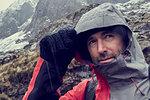 Male hiker pulling hood up in sleeting snow capped mountain landscape, close up, Llanberis, Gwynedd, Wales