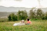 Girl sitting and petting labrador dog in scenic field landscape, Citta della Pieve, Umbria, Italy