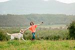 Girl running with labrador dog in scenic field landscape, Citta della Pieve, Umbria, Italy