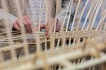 Young female basket maker weaving in workshop, mid section