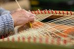 Young female basket maker weaving in workshop, close up of hands