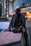 Stylish man sitting on concrete bench, Milan, Italy