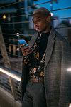 Stylish man leaning against bridge railings using cellphone, Milan, Italy