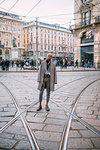 Stylish man posing on tram tracks in piazza, Milan, Italy