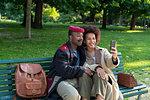 Loving couple taking selfie on park bench, Milan, Italy