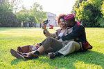 Couple sitting on grass taking selfie, Milan, Italy
