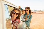 Portrait happy multi-generation women at van on sunny beach