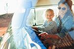 Happy mother and daughter driving van