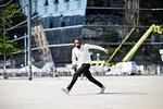 Man with headphones dancing in city