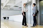 Colleagues talking near elevator