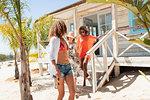 Women descending sunny beach hut steps