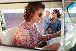 Multi-generation women with map in van